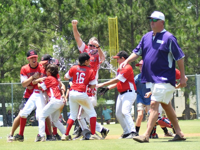 Screven County coaches Logan Smith and Chris Grovenstein celebrate with their 12-and-under baseball players with cups of water after their 11-1 triumph in the June 25 state title game as opposing Fitzgerald/Ben Hill coach Daniel Cowan walks across the diamond toward his team's dugout.