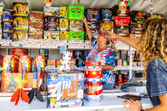 Shonda Casey-Ogans helps a customer pick out some of the stand's best fireworks. Locally owned and family-run for 35 years, B&C Fireworks, located on 14th and Virginia, supports local baseball and softball teams and veterans with proceeds from its sales.