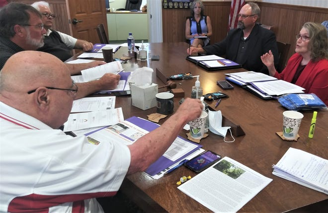 Judy Wortham-Wood and Craig Sanders of the Mental Health Recovery Board of Wayne and Holmes Counties (at right) discuss ongoing situations with the Holmes County Commissioners Ray Eyler, Rob Ault and Joe Miller (at left).