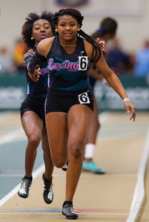 Lexington's Aquariah McIntosh is shown here taking the baton from Ny'Lasia Brown in the 2020 2-A indoor 4x200 relay. Both helped lead Lexington to victory in the 4x100 and 4x200 in the 2-A state championships on Saturday at North Carolina A&T. [Donnie Roberts for The Dispatch]