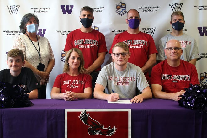 """Continuing his academic and athletic career at St. Joseph's University is recent Wallenpaupack Area graduate James """"Jake"""" Carrubba. On hand for the signing ceremony were (seated, from left): Kyle Carrubba, Tara Carrubba, Jake Carrubba, Chris Carrubba. Standing are: Athletic Director Ann Marie Simons, Assistant track & field Coach Dave Miller, head track & field Coach Mark McHugh, and head cross country coach Steve Brown."""