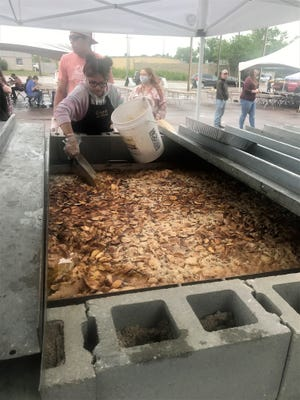 Rich Bennett's daughter, Brooke, tends to the World's Largest Peach Cobbler at the Peach Festival in Sioux Falls.