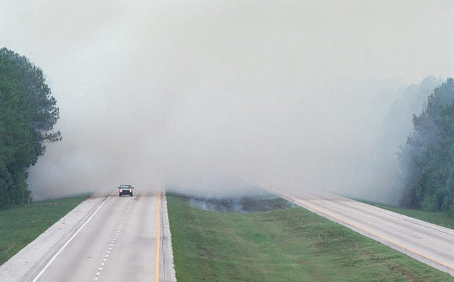 A truck emerges from smoke on the northbound lane of I-95 just south of the St. Johns County/Flagler County line during the 1998 wildfires that wreaked havoc on Northeast Florida.