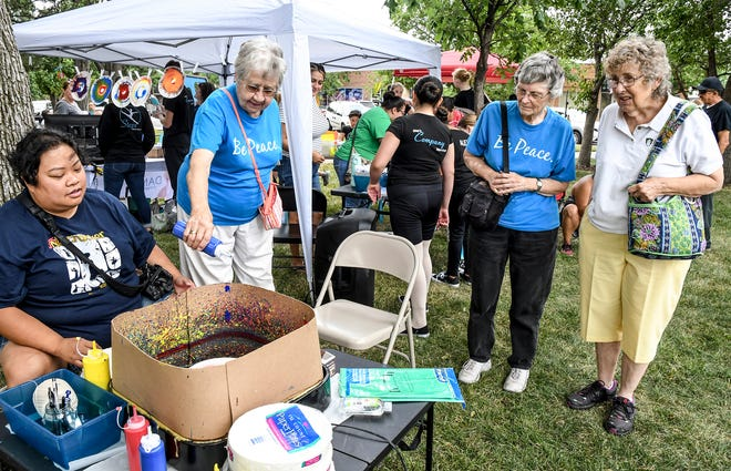 Sister Rose Mary Stein, second from left, places a few drops of blue paint on a spinning paper plate Saturday while trying her hand at creating spin art at one of the children art booths during Art in the Park at Stevens Park.  Sompathana Phitsanoukahn, left, gives Stein advise on how to do the process while running the activity.  Thirty vendors and artists filled the park for the annual event, with 18 hands-on activities available for children and adults to participate in.