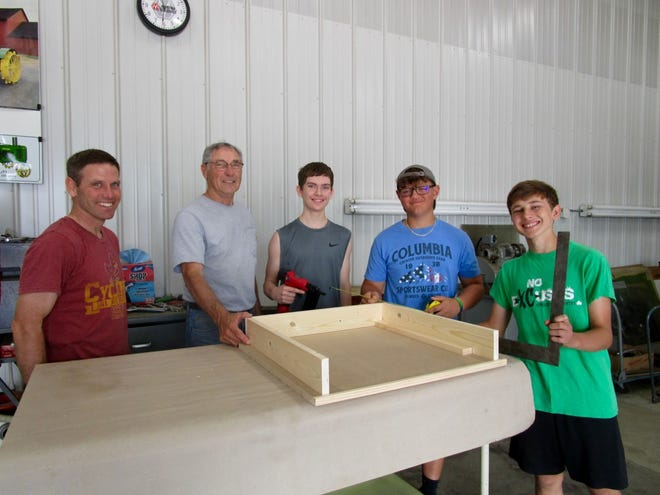 Barney Gehl, left; Tom Hitzhusen, Max Biddle, Bryce Johnson and Dylan Gehl are shown finishing work on one of the desk shelves. The desk-building project was part of Grace in Action from Grace United Church in Geneseo.