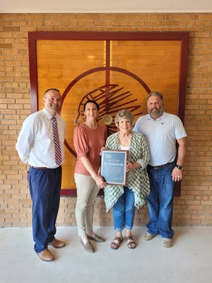 Annawan School Superintendent Matt Nordstrom, left; Kim Park, board member; Becky (Frankenreider) Bengtson and Jerad Heitzler, school board president, are shown with the plaque presented to Becky (Frankenreider) Bengtson in honor of her late husband, Jim Frankenreider, for being inducted into the Illinois High School Football Coaches Association Hall of Fame. Kim Park is the daughter of Jim and Becky Frankenreider, and currently serves on the Annawan School Board.