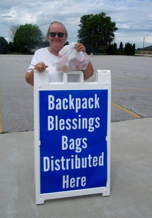 """Sharon Carton, director of Geneseo's Backpack Blessings program, is shown holding one of the food packages in the student parking lot at Geneseo High School, the summer distribution site for Backpack Blessings, which also is the pickup point for the summer """"Lunch Box"""" program, which provides lunches for young people in the Geneseo and surrounding communities."""