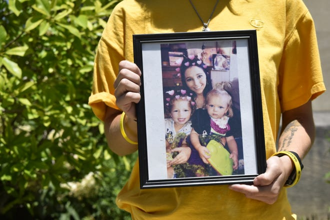 Mady Lohman holds a picture of her sister, Jordyn Graham, with Graham's daughters, Wynter and Wysper. The photo  was taken about six months before Graham was shot and killed in 2020.