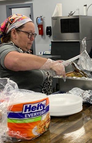 Volunteer Sandi Imel helps serve a Friday dinner at Kingdom Culture Church's Overflow Cafe.