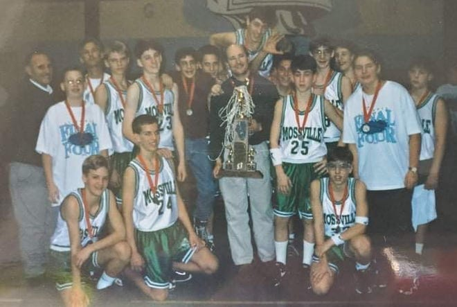 Former Mossville coach Dale Lindholm holds an Illinois Elementary School Association state basketball trophy after helping the Warriors to second place in 1996.