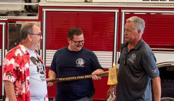Fire Lt. Chip Davis, left, is handed a commemorative axe by Macedonia Firefighter's Association President Michael Jaskolka, center, and Fire Chief Brian Ripley.