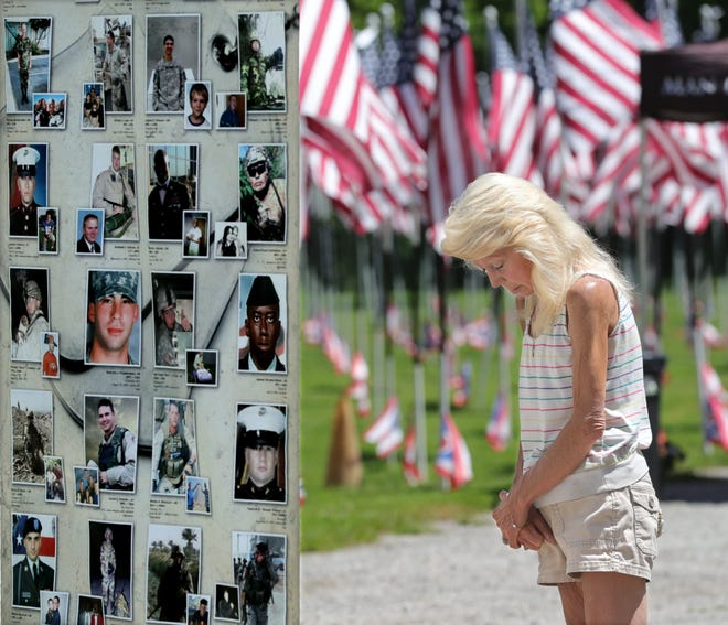 Macedonia resident Michelle Gaski says a prayer while viewing the traveling memorial dedicated to the soldiers who made the ultimate sacrifice in the war on terror since September 11, 2001. Northfield VFW Post 6768 hosted the display Thursday through Sunday last week.