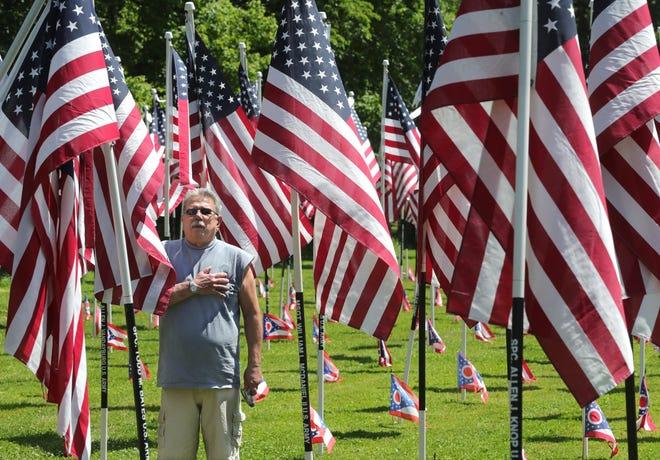 """Northfield VFW Post 6768 officer Joe Volny pauses from fixing a flag display as the National Anthem is played during a ceremony Thursday as the """"Remembering our Fallen"""" exhibit is open to the public at the post in Northfield Center."""