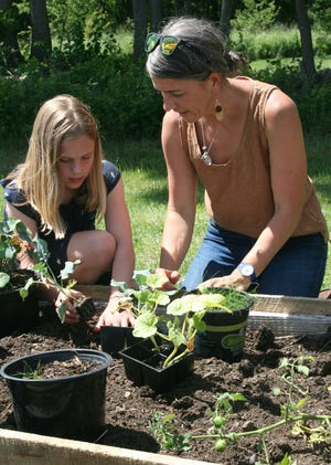 Erika Dempski, 10, and Jamie Aspenson, Overlook Farm's new executive director, work in one of the planting boxes at Overlook Farm recently.