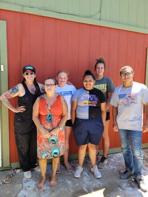 """Las Animas artist Lynette Wolfe, left, and a group of student volunteers from the Las Animas school district helped paint the house of Josefina Sisneros, second from left, as part of the """"Paint and Connect"""" Project."""