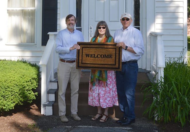 Cazenovia College Executive Vice President David Bergh, left, holds out the welcome mat at 43 Linckaen St., the college-owned campus house being renovated as a suitable home for New American families. With him are Carolyn Holmes, center, and David Holmes, of Cazenovia Welcomes Refugees.