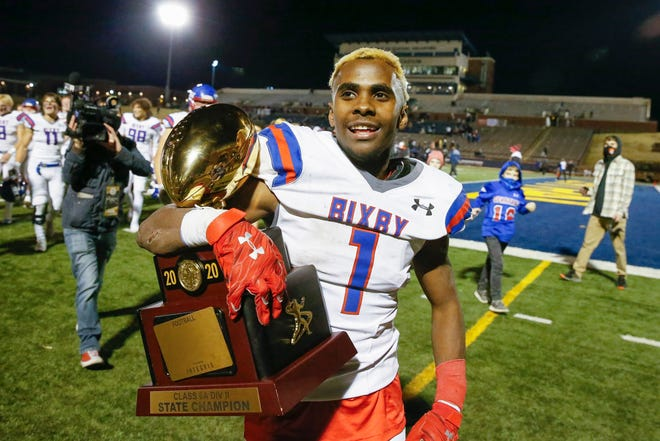 Bixby's Braylin Presley walks off the field holding the Class 6A-II championship trophy after defeating Choctaw on Dec. 5 in Edmond.