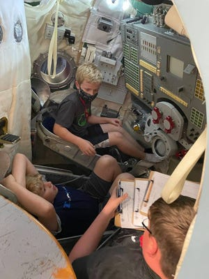 Dylan Lehman, 12, of Pratt, sits in a Russian space capsule, working with his teammates at Space Camp to decode operation buttons in a foreign language.