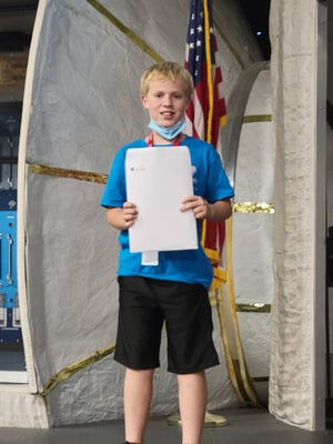 Standing in front of an ISS mockup, Dylan Lehman of Pratt, holds graduation certificates and commendations from a Live and Thrive space camp he attended last week at the Hutchinson Cosmosphere.