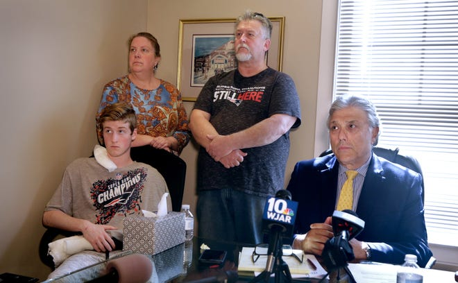 Dominic Vincent, 18, of West Greenwich, left foreground, who was shot by off-duty Pawtucket police officer Daniel Dolan last week, listens at Monday's news conference. Behind him are his parents, Lisa and Robert Vincent. At right is his lawyer, James Howe.