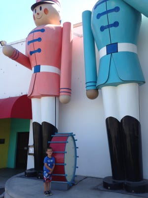 Tim Viall's grandson Jack stands outside the Children's Museums giant tin soldiers at its entrance.