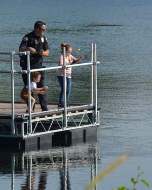 An Aurora police officer fishes with two young participants of the Portage Park District's Fish With a Cop event on June 26.