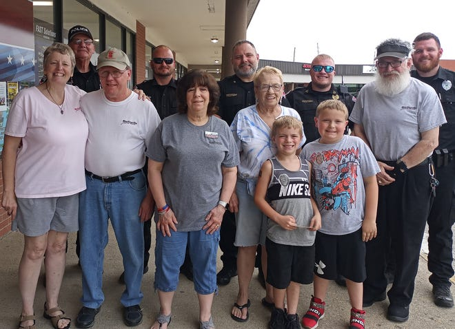 Martinsville Police Officers, members of the Martinsville Crime Watch and a couple of local children pose for a photo during the recent Cupcakes with a Cop event at Beefcake Burgers.