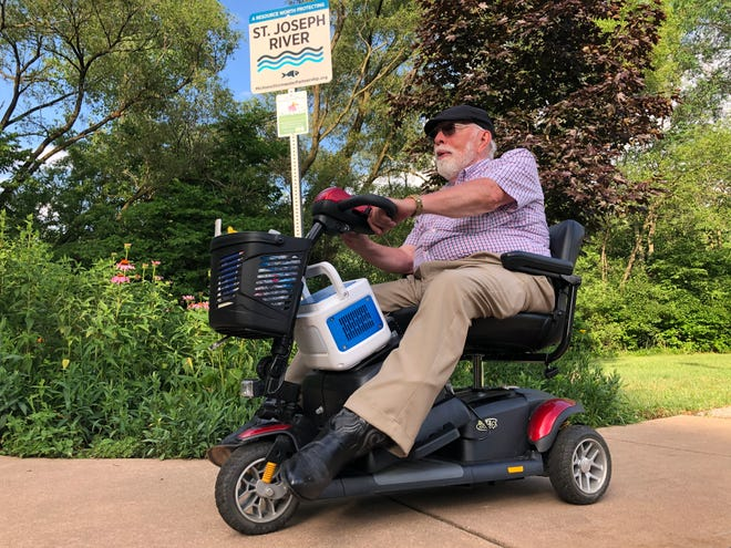 Ken Daniel of Niles rides his motorized scooter Sunday on the Riverside Trail northwest of Keller Park in South Bend.