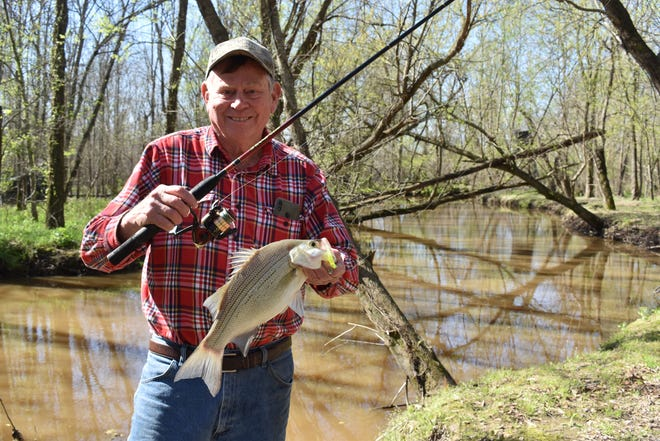 Luke Clayton with a feisty white bass. After reading this week's column, if your interest in fishing is not sparked, Luke suggests you might think about scheduling your next Tee Time at the golf range.