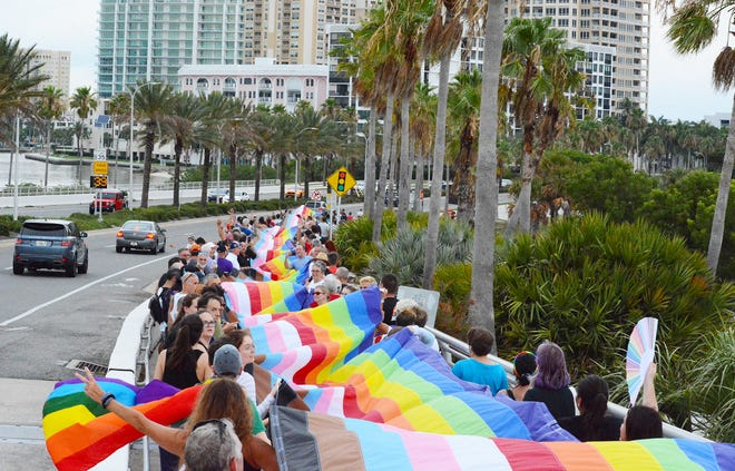 Demonstrators walk down Ringling Bridge with a 375-foot LGBTQ Pride flag in honor of Pride Month.