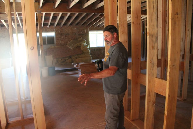 Beacon of Hope volunteer Tom O'Gorman gives a tour of  a homeless shelter being built by the group on Saturday.