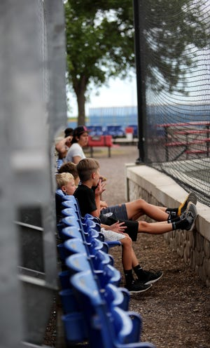 Several fans sit in the front row to watch the game between Groton Locke Electric and Redfield Dairy Queen at Locke Karst Field in Groton. American News photo by Jenna Ortiz, taken 06/27/2021.