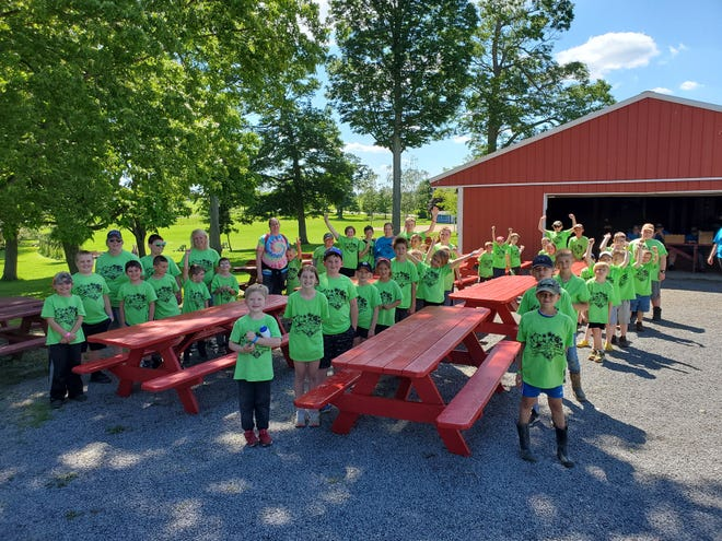 Cub Scouts, leaders, and the Scouts BSA junior staff members painted the tables during day camp.