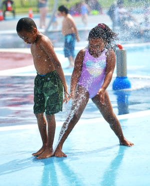 Siblings Desharn Minton, 8, and Deseri Minton, 6, of Worcester, cool off Monday at the spray park in Cristoforo Colombo Park on Shrewsbury Street.