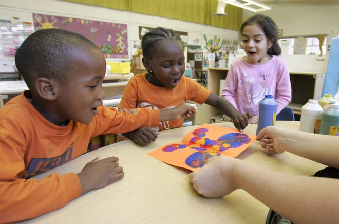 Preschoolers look at the butterfly that one of them made for a Mother's Day card at a publicly funded preschool class in California.