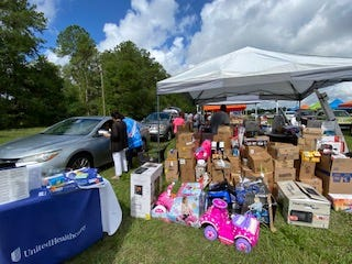 The drive-thru giveaway sponsored by Ivory's Place Inc. and Women Working with Women Inc. drew 300 cars and 700 families Saturday.