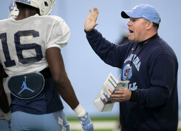 Defensive coordinator Jay Bateman, right, gives instructions to North Carolina players, including former defensive back D.J. Ford, left, during a preseason practice in August 2019.
