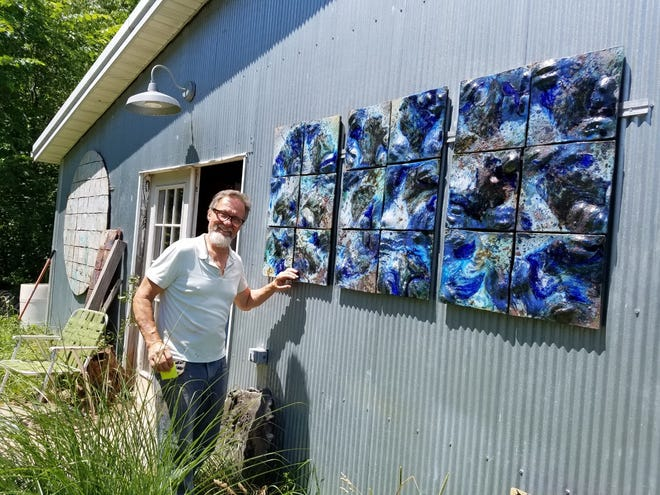Ceramic artist Tom Radca is shown with a piece that features the results of his efforts to use blue bottles and tempered glass to create the appearance of water. TIMES-REPORTER/NANCY MOLNAR