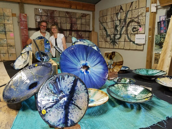 Artist Tom Radca and assistant Margit Stewart stand amid some of the pieces at Radca Ceramics, where a two-weekend open house continues Thursday through Sunday.  TIMES-REPORTER/NANCY MOLNAR