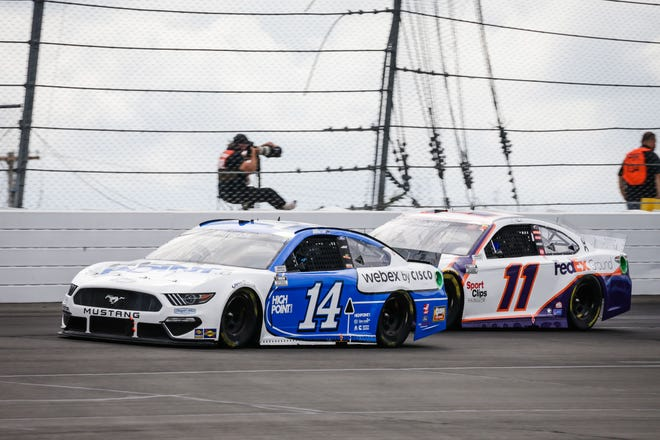 Mitchell's Chase Briscoe (14) duels with NASCAR Cup Series points leader Denny Hamlin Saturday at Pocono Raceway.