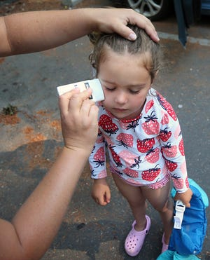 Angela Tilley applies sunscreen to her 4-year-old daughter Kinsley's face before they hit the beach at Island Lake Park Monday.