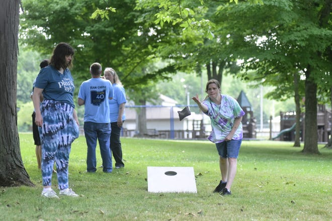 Hunter Labue watches as Carie Gebhardt tosses a cornhole bag Monday morning during a special olympics celebration at Aumiller Park in Bucyrus.