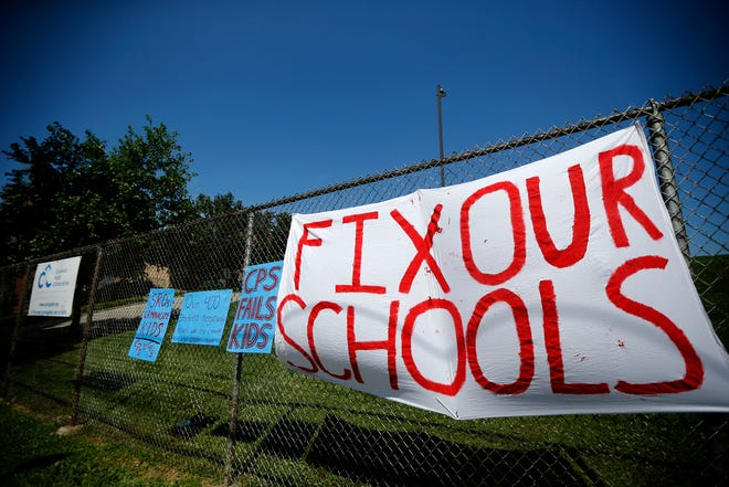 Students from the Young Activists Coalition clip a sign to the fence near the main entrance of the Cincinnati Public Schools administrative building in the Corryville neighborhood of Cincinnati on Monday, June 28, 2021.