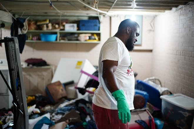 Gary Whitfield, 40, of Detroit cleans his basement in the Jefferson Chalmers neighborhood after rainstorms caused a flood in his basement in Detroit on Sunday, June 27, 2021.