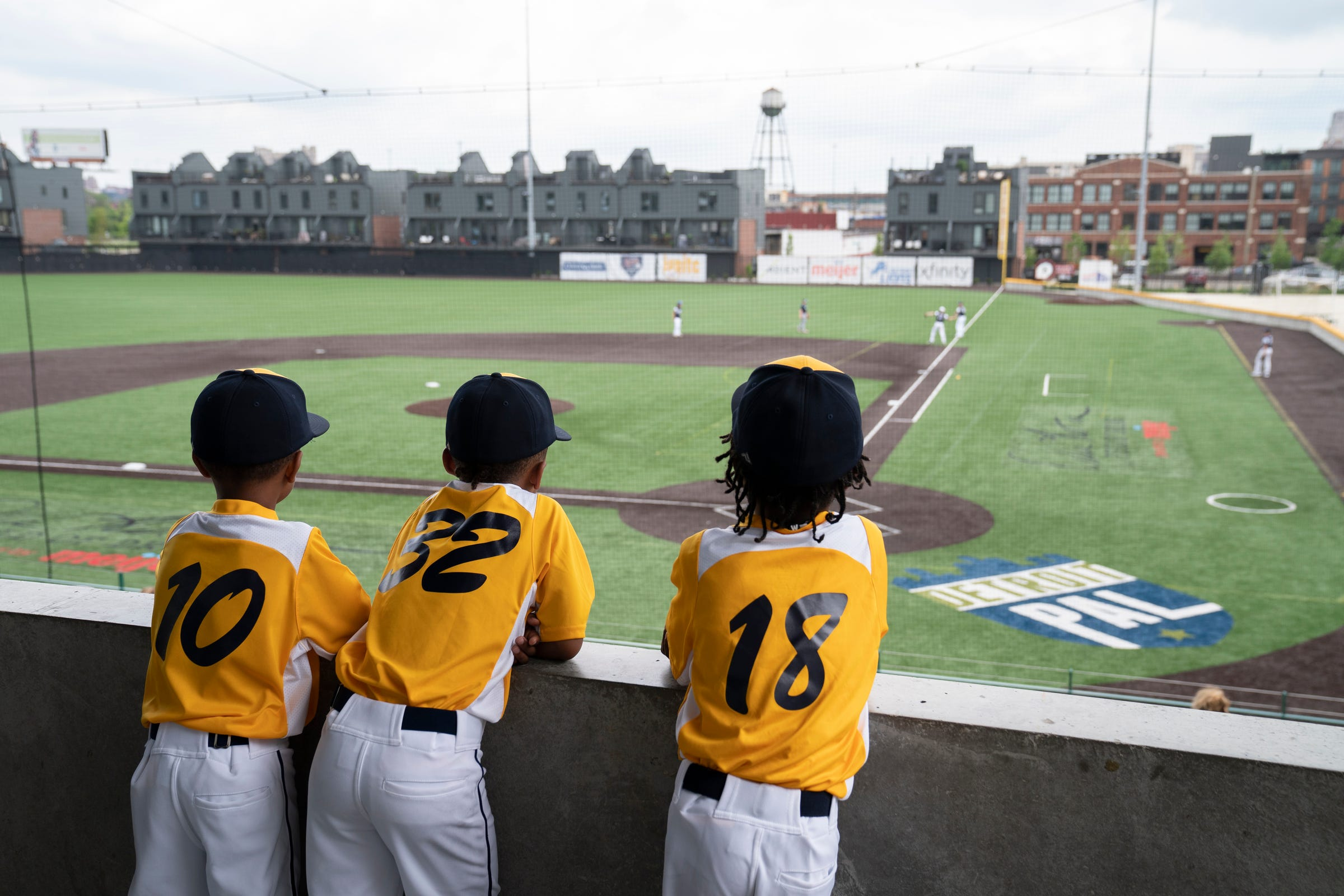 Nolan Doss, 6, of Farmington Hills, left, looks onto the Detroit Police Athletic League (PAL) field with fellow teammates Michael Anderson, 7, of Farmington Hills and Matthew Williams, 6, of Detroit as PAL opens to some good news from the state of Michigan Monday, June 28, 2021. Legislators from the Michigan House of Representatives announced a new $15 million commitment to PAL, specifically PAL's new Community Connection Initiative.