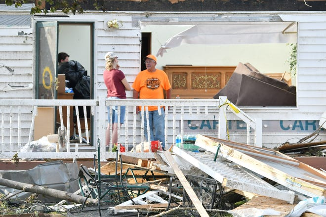 Steve Lepeak, 65, at right, stands on the porch of what is left of his home the day after a tornado devastated homes along Grindstone Road in Port Austin, June 27, 2021