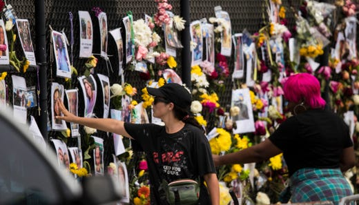 A woman places her hand on a photo at the memorial site for those missing from the Champlain condo collapse in Surfside, Fl on Monday, June 28, 2021.