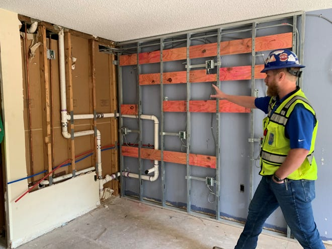A construction worker shows a former motel room that's being gutted to soon serve as an affordable housing option in Charlotte, North Carolina.