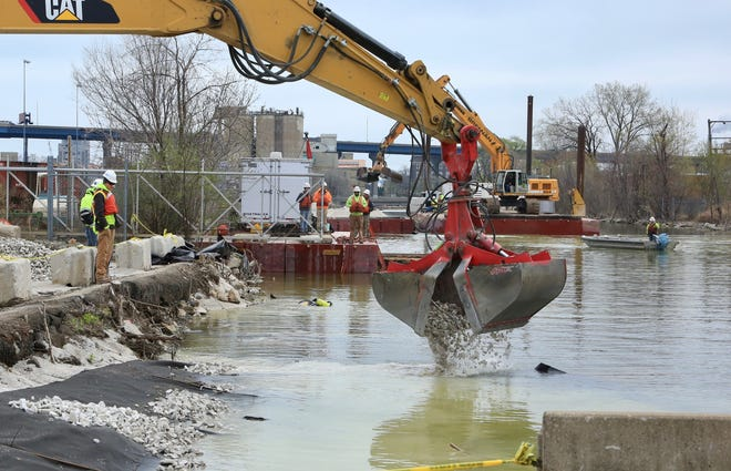 Heavy equipment deposits gravel on the west end of the Burnham Canal in Milwaukee, part of an effort to clean up the waterway.