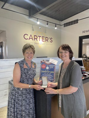 The winner of the 2021 Red White Blue diamond pendant is Shena Loftis of Thornfield, Missouri. Pictured, from left: Beth Carter presents the pendant to Loftis.